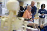 Dr. Alan Spees checks on Donald Roberts during a rehabilitation session at Spalding Rehab Hospital...