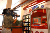 (Denver, Colo., May 24, 2004) Channel 4 cameraman photographs a machine that sells DVD's at...