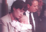 Kathleen Bohland holds her baby Calla Lopez next to Denver D.A. Bill Ritter talks to the press...