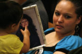 (from left) 2 year-old Renee Salas (cq) touches a portrait of her great-aunt, Roberta Neville (cq)...
