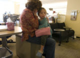 Rocky Mountain News copy editor Kim Humphreys holds her daughter Clara, 4, in the newsroom of the...