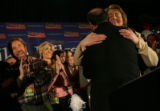 Mike Huckabee embraces wife Janet after addressing a crowd in the ballroom at the Embassy Suites...
