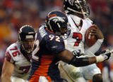Atlanta Falcons' #7, Michael Vick,right, spins away from Denver Broncos' #92, Marco Coleman, left,...