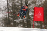 Ted Ligety goes over the lip of a jump on the bottom part of the course in the downhill portion of...