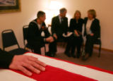 Kyle Anderson, (L), rests his hand on the casket of his brother Navy Hospital Corpsman Christopher...