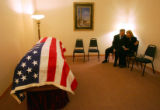 Rick Anderson comforts his wife Debra Anderson as they sit with the casket of their son Navy...