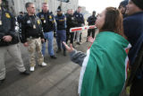 Lupe Tapia, cq, of Greeley yells at federal ICE agents who stand guard in front of the Swift &...