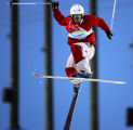 Canadian Moguls skiier Chris Wong tries to gain control of his rotation in the air during his...