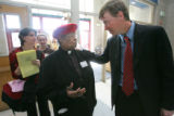 Pastor Josephine Falls chats with Denver Mayor John Hickenlooper while waiting to vote at a...