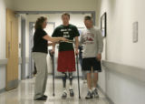 Tyler Carron, walks with the help of his physical therapist Sylvia Boedeker and his father Bruce...
