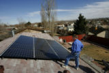Matthew Caryofilles, owner of SALT Electric LLC., checks up on some recently installed solar...