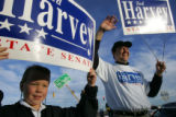 Jack Harvey, 9, son of Colorado state Representative Ted Harvey, right, holds a sign for his dad...