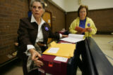 Election judges Joyce Knutson, left, and Darlene Cassel prepare a voting machine for precinct 236...