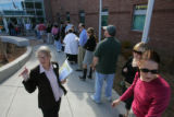 Poll-watcher Paula Vandusen, informs voters about other voting centers available to them instead...