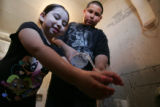 Michael Garcia,12 pours water for his sister Marissa Garcia , 5, as she washes her hands after...