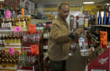 Dawit Beyene (cq), owner of E & S Liquors, 6460 E. Yale Ave, in his store restocking product, ...