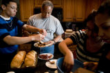 Branden Fox, 15, (cq) and his father John Fox (cq), grab bites of chicken in the kitchen, while ...