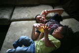 Joshua, 11, (cq) plays football with his younger sister Lanae, 4, (cq) in their living room. With...