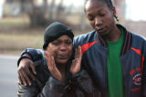Lekasha Kirk (cq),left,  is led away as Denver police investigate the scene of a deadly shooing...