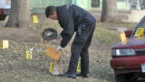 Denver police place  a hat into an evidence bag at  the scene of a deadly shooing outside a home...