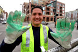 Denver City and County traffic worker Fernando Hurtado (cq) shows green after painting  fresh...