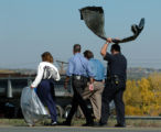 (WHEAT RIDGE, CO. OCTOBER 12, 2004)  Investigators carry evidence from the scene where a  tractor...