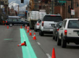 Traffic moves past Coors Field along  fresh green paint on a three lock stretch  Blake Street ...