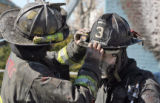 L to R: Denver firefighters Rich DeHerrera (cq) and Doug White (cq) help each other during a house...