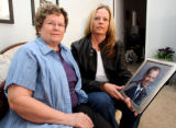 PHOTO BY CHRISTOPHER TOMLINSON--Loa Richards, left holding a photo of her late husband Warren...