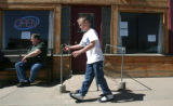 Zane Bearfoot, left,  skates on his roller shoes as Robert Lowe, owner, cook, and dishwasher at...