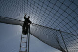 Chris Cyr (cq) works on the netting at his batting range, Batter Up - 200 Peoria St., Wednesday...