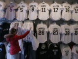 Jacy Bloom (cq) looks at jerseys at the SportsFan shop outside of Coors Field on Thursday...