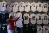 Jacy Bloom, of Denver, looks at Colorado Rockies jerseys at the SportsFan shop next to Coors Field...