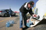 Eric Treinen, with the Alomosa FD,  fills water jugs for Maria Lujan, at a water distrubution...