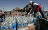 Red Cross worker Becca Thompson unloads bottled water at a water distrubution center outside the...