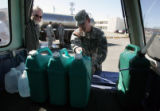 Army National Guardsman Pfc Steven Snow, loads water containers for David Roepke (left) filled...