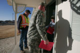 CDOT worker Ryan Reynolds, left, and National guardsmen, Private Nathaniel Hale   speak with...
