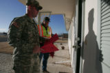 National guardsmen canvas a neighborhood to make sure everyone knows that the city is  purging the...
