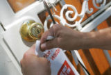 John Aguilar, of Denver Water, places a warningon a door for watering between 10 am and 6 pm in...