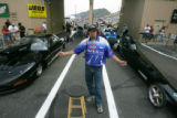 Dragmaster Tom Stark directs cars forward during the Super Comp qualifier at the Mile-High...