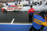 Driver Larry Morgan smokes his tires in the pro stock car qualifier at the Mile-High Nationals at...