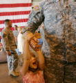 Ava Bauer, 5, hangs on the arm of her dad, Timothy Bauer, at Buckley Air Force Base during a...