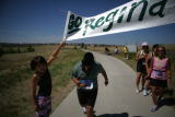 Regina Terry (cq) runs through a banner her husband Jack (cq)  and daughter Madison, 9 (cq) hold...