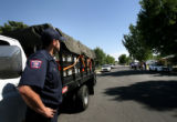 (PG02486) Sam Gillan, of the Denver Fire Department, waits by a truck loaded with 50 cases of...