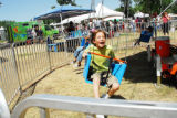 Will Haack, 8, of Longmont, laughs as he spins in a circle on a swing ride at Rhythm on the River...