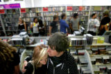 Grace West, 18, and Bryce Hoops, 20, console each other at Independent Records following Johnny...
