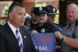 (122) Denver Police officer Rich Jones, center, listens in to the remarks by Bill Young, the...