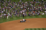 Fans from the outfield pour onto the field to watch fireworks,Thursday evening, July 3, 2008,...