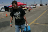Mario Garramone, 21, (cq) a superstock racer from Littleton carries his gas can back to his car...