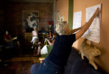 Jana Everett (cq) of Denver, posts notes from group discussions on her wall as her cat sneaks by....